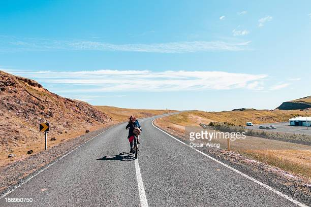 A young girl is cycling on the highway