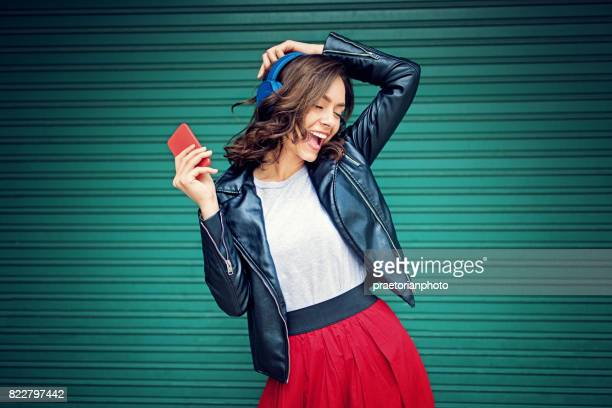 young girl is dancing and listening the music - bluetooth stock pictures, royalty-free photos & images