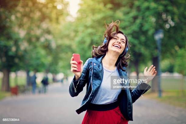 young girl is dancing and listening the music till walking in the park - music photos et images de collection