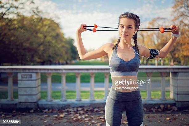 young girl is doing resistance band exercises in the park - train band stock photos and pictures