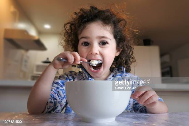 Young Girl is Eating Breakfast/Dinner in the Morning/Evening