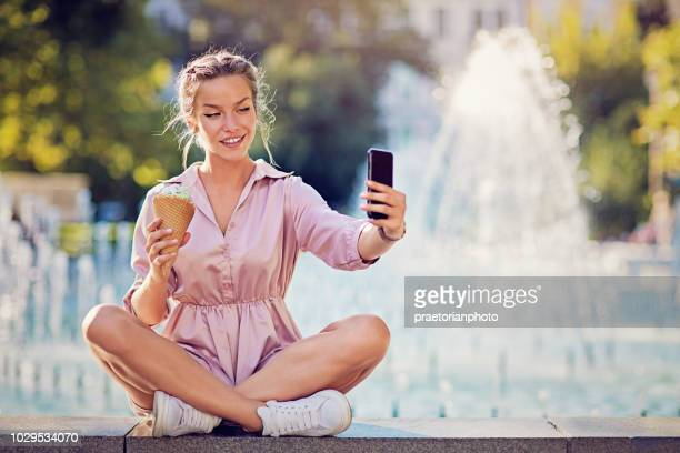 young girl is eating ice cream and taking selfie/making video call at the city fountain - girls flashing camera stock pictures, royalty-free photos & images