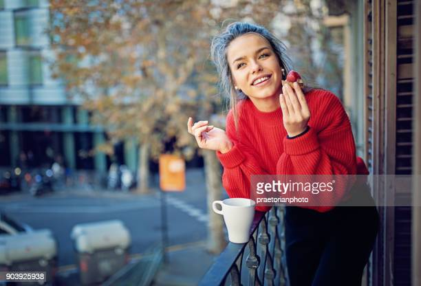 Young girl is eating strawberry cake and drinking coffee at the balcony in the morning