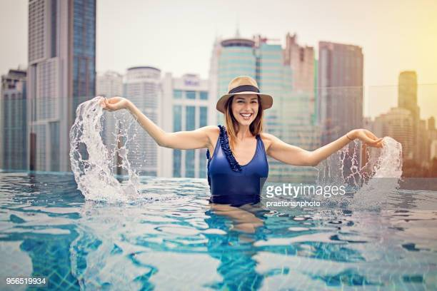 young girl is enjoying the water on the rooftop swimming pool - malaysia beautiful girl stock photos and pictures