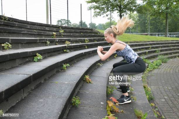 A young girl is exercising and makes squats on a staircase Staged picture on August 10 2017 in Duelmen Germany
