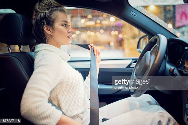 young girl is fastening her seat belt in a rainy day - driver stock pictures, royalty-free photos & images