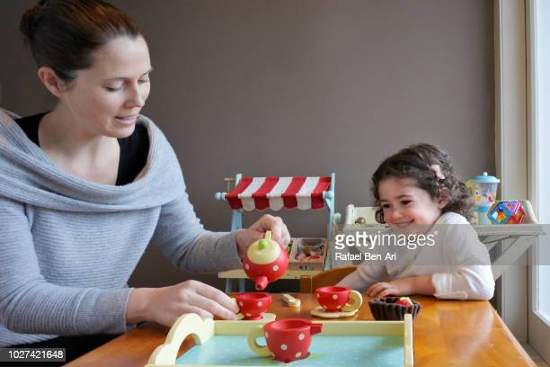 young girl is having a tea time party with her mother - rafael ben ari stock-fotos und bilder