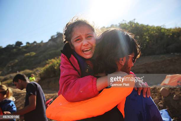 A young girl is helped moments after she arrive with other Syrian and Iraqi migrants on the island of Lesbos from Turkey on October 14 2015 in...