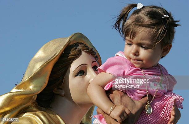 A young girl is introduced to a Virgin statue during the procession celebrating the Feast of the Assumption marking the Virgin Mary's ascension into...