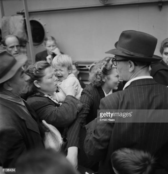 A young girl is less than impressed as she arrives at Ellis Island New York with other displaced persons from postwar Europe on board the USS General...