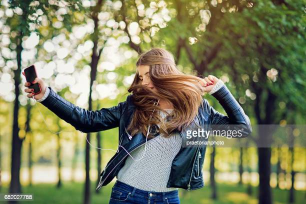 Young girl is listening the music and dancing in the park