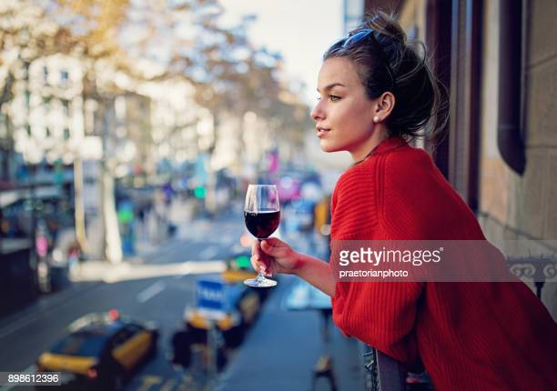 Young girl is looking the city at the balcony and drinking red wine