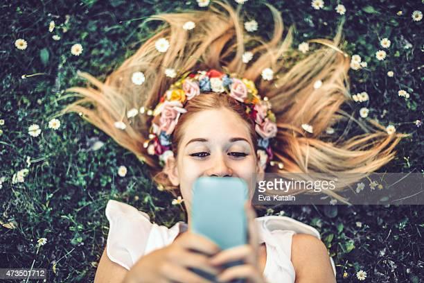 """Young girl s'están recostadas en el césped y tomando los """"selfies"""""""