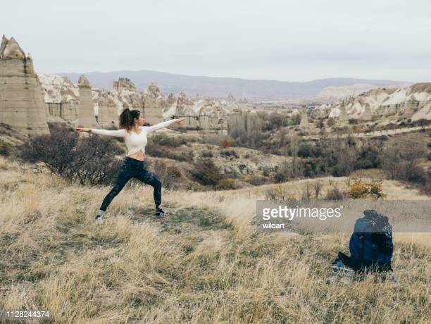 young girl is meditating in red and rose valley in goreme in cappadocia in turkey - rock hoodoo stock pictures, royalty-free photos & images