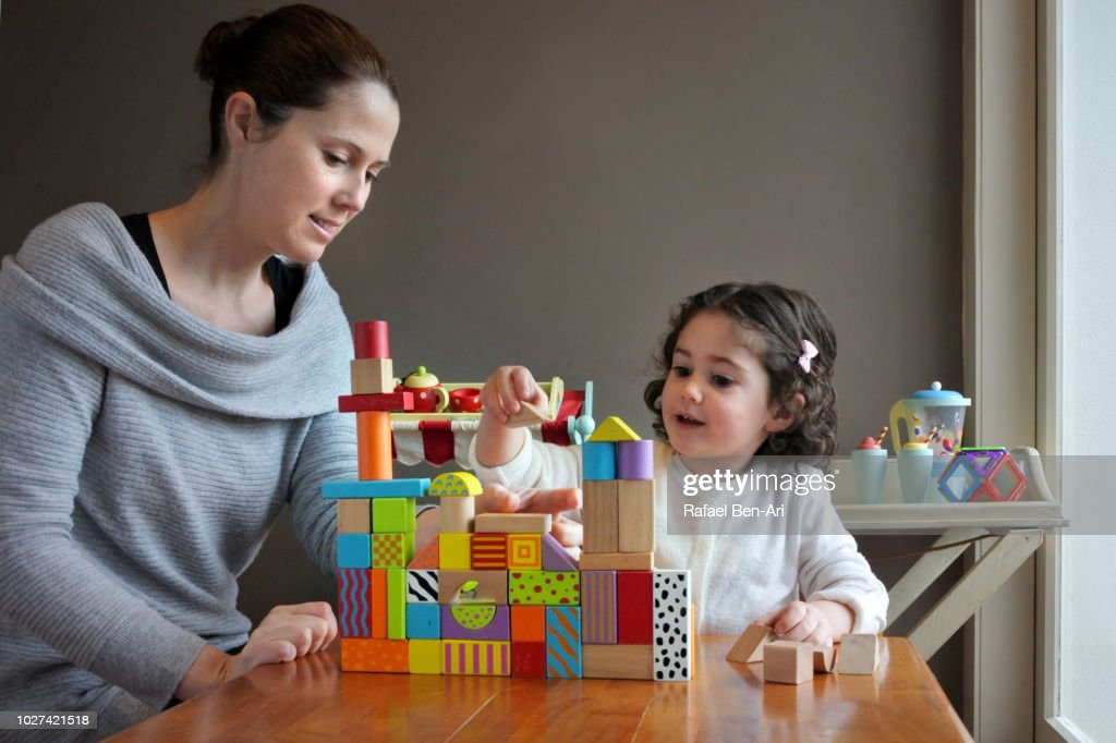 Young Girl is Playing Building Bricks with her Mother : Stock Photo