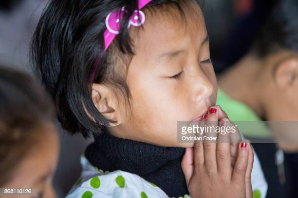 A young girl is praying with her eyes closed while a ceremony inside a church in Kalimpong