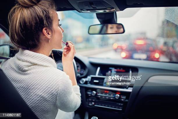 Young girl is putting lipstick in the traffic jam in rainy day