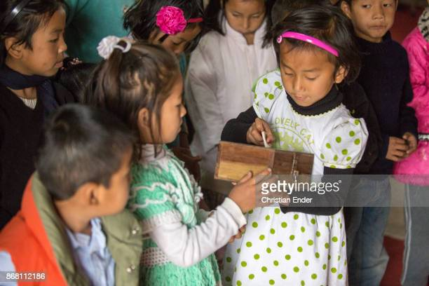 A young girl is putting money inside a donation box after a ceremony inside a church in Kalimpong