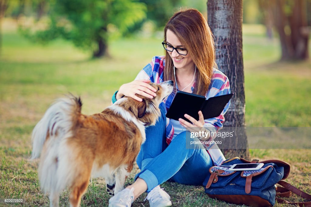Young girl is reading ebook and stroking her dog in the park : Stock Photo