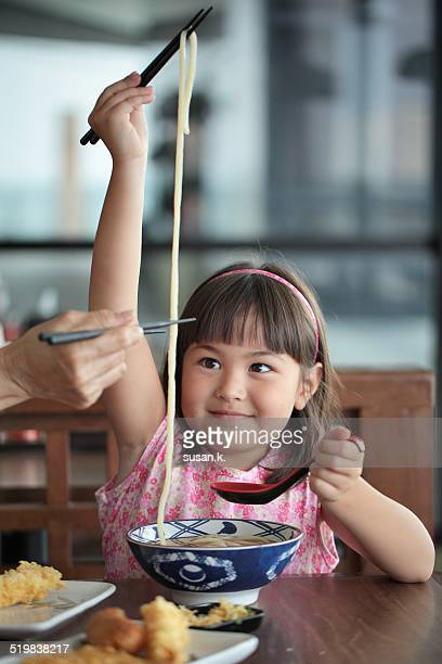 Young girl is ready to eat her big bowl of udon.