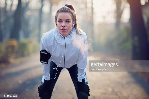 jong meisje rust uitgeput na run in mistige ochtend - winter sport stockfoto's en -beelden