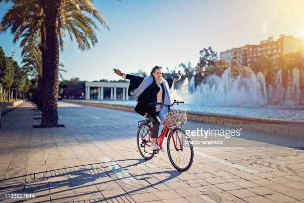young girl is riding a bicycle without hands in the park - spread wings stock pictures, royalty-free photos & images