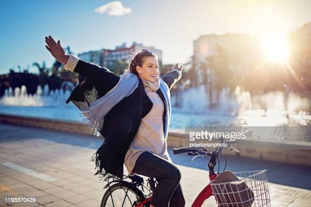 la jeune fille monte un vélo sans mains dans le stationnement - velo humour photos et images de collection