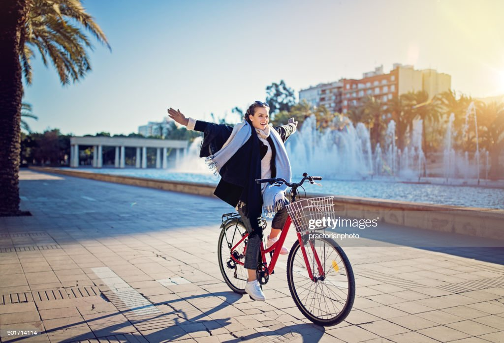 Young girl is riding a bicycle without hands in the park : Stock Photo