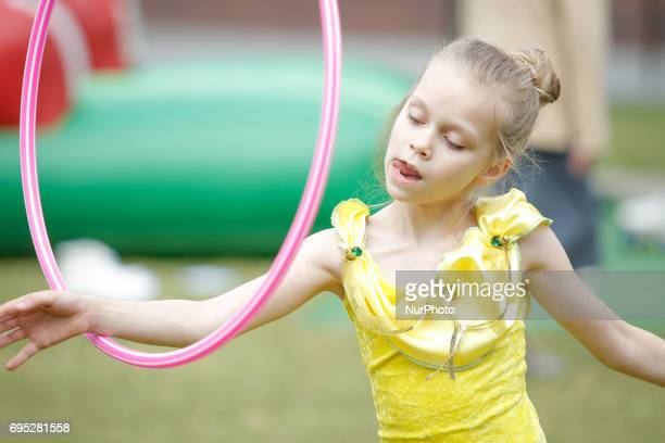 A young girl is seen concetrating while playing with a hula hoop during an amusement fare in Bydgoszcz Poland on 10 June 2017