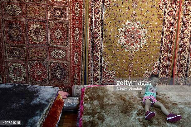 A young girl is seen playing at a carpet shop in a Ramadan bazaar stall on July 22 2014 in Singapore One of the five pillars of Islam fasting during...
