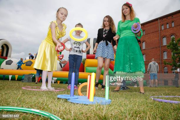 A young girl is seen playing ring toss during an amusement fare on the Mill Island on 10 June 2017