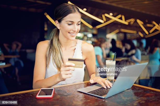 Jong meisje is online winkelen in het café met laptop en haar creditcard