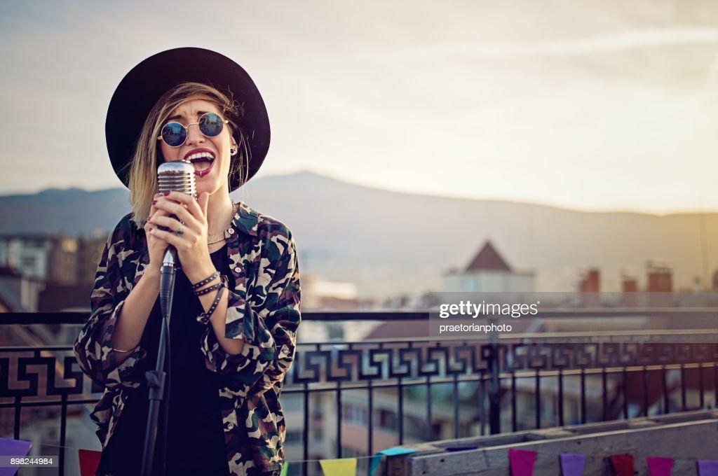 Jovem vai cantar na festa de terraço no telhado : Foto de stock
