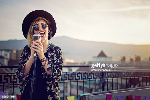 young girl is singing on the roof terrace party - singer stock pictures, royalty-free photos & images