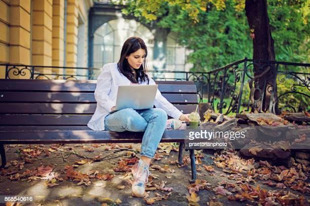 Jeune fille est assis sur le banc, travaillant sur son ordinateur portable et boire smoothy