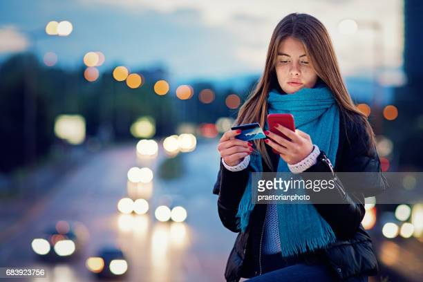 Young girl is sitting on the bridge and shopping online