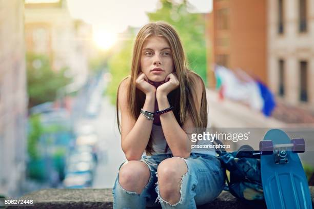 young girl is sitting sad at the front of the city sunset - cruel stock pictures, royalty-free photos & images