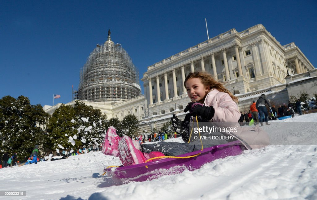 TOPSHOT - A young girl is sliding on the West Lawn of the US Capitol on January 24, 2016 in Washington. Millions of people in the eastern United States started digging out Sunday from a huge blizzard that brought New York and Washington to a standstill, but the travel woes were far from over. The storm -- dubbed 'Snowzilla' -- killed at least 18 people after it walloped several states over 36 hours on Friday and Saturday, affecting an estimated 85 million residents who were told to stay off the roads and hunker down in doors for their own safety. / AFP / Olivier Douliery