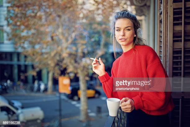 young girl is smoking cigarette and drinking coffee at the balcony in the morning - little girl smoking cigarette stock photos and pictures