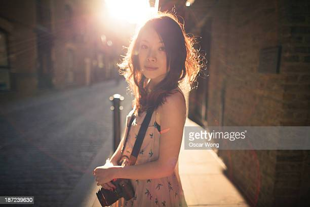 A young girl is standing against the sunlight