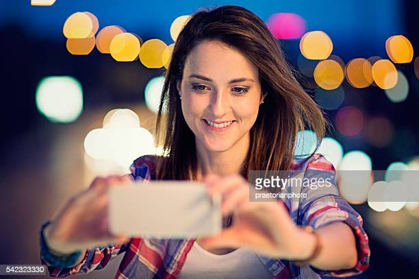 Young girl is taking selfie in the night