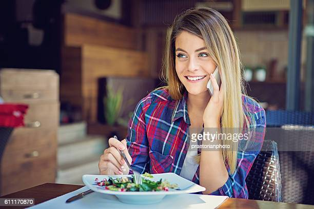 Young girl is talking using her mobile phone in restaurant