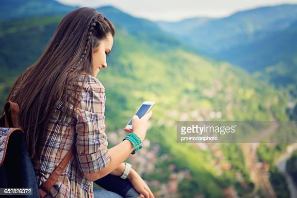 young girl is texting till resting on the top of the peek - valle foto e immagini stock
