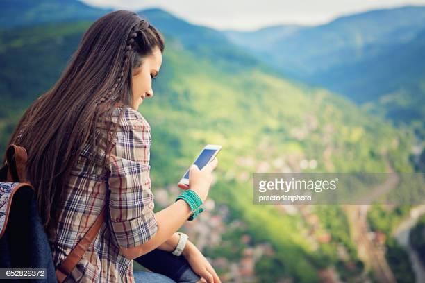 la ragazza sta messaggiando fino a riposare sulla parte superiore della sbirciatina - valle foto e immagini stock