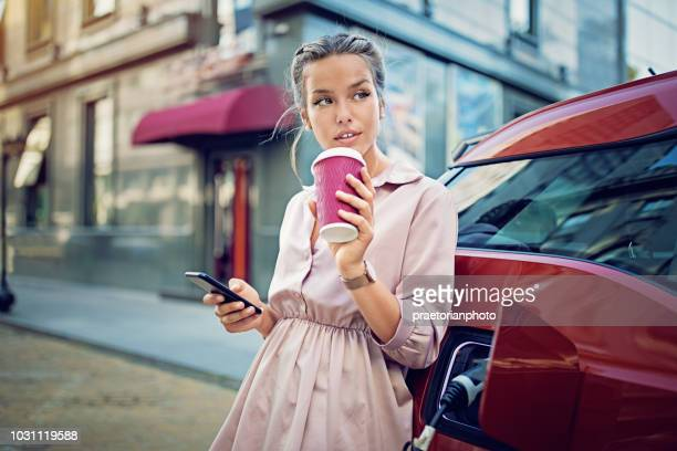 young girl is texting until waiting her electric car to charge - hybrid car stock photos and pictures