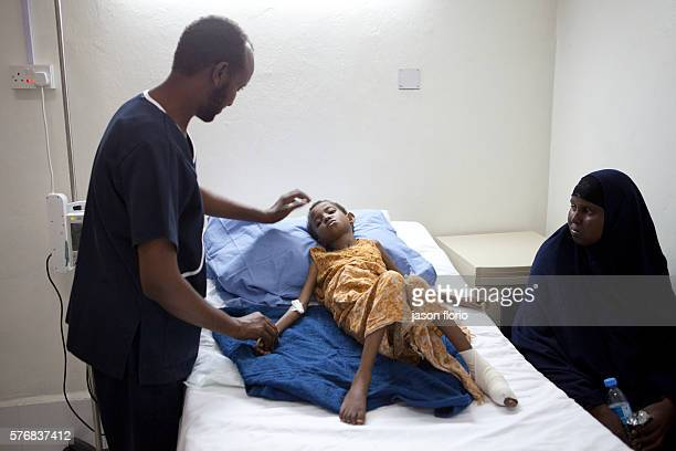 A young girl is treated inside Villa Somalia Clinic for an injured foot as her mother looks on March 2011