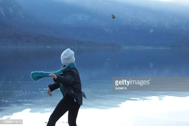 young girl is trying to do stone skipping by the lake. - skipping along stock pictures, royalty-free photos & images
