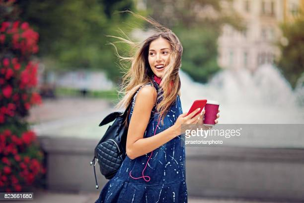 Young girl is walking in the city in the windy day, holding a coffee and mobile phone