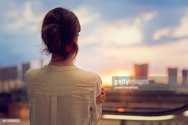 young girl is watching sunset over tokyo - avondschemering stockfoto's en -beelden
