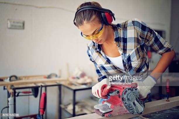 Young girl is working with sander in small family carpenter factory
